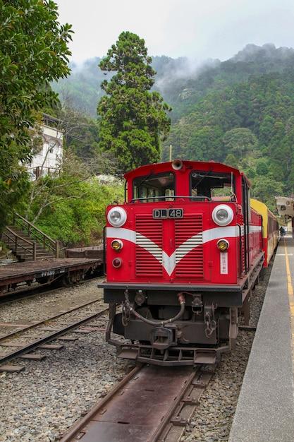 Velho trem vermelho na linha alishan (descendo) volte para a estação de trem de chiyi em dia de neblina. Foto Premium