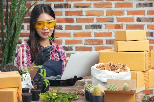 Venda de plantas online; mulher segurando um vaso de planta e usando laptop Foto gratuita