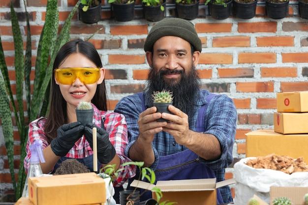Venda de plantas online; vendedores sorrindo e segurando o vaso de planta nas mãos Foto gratuita