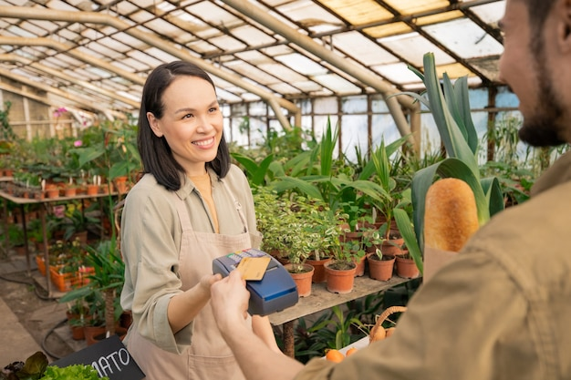 Vendedor asiático amigável sorridente segurando um terminal de pagamento enquanto agradece ao cliente pela compra na loja da fazenda Foto Premium