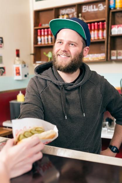 Vendedor com cachorro-quente em lanchonete de fast food Foto Premium