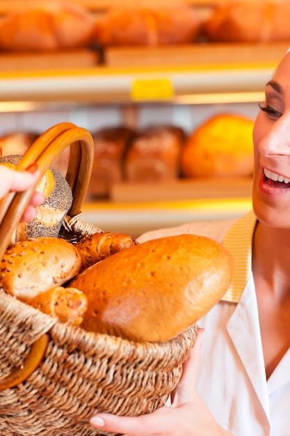 Vendedor com cliente feminino na padaria Foto Premium