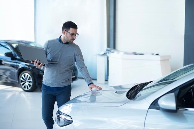 Vendedor de carros com laptop verificando as especificações do veículo no showroom da concessionária local Foto gratuita