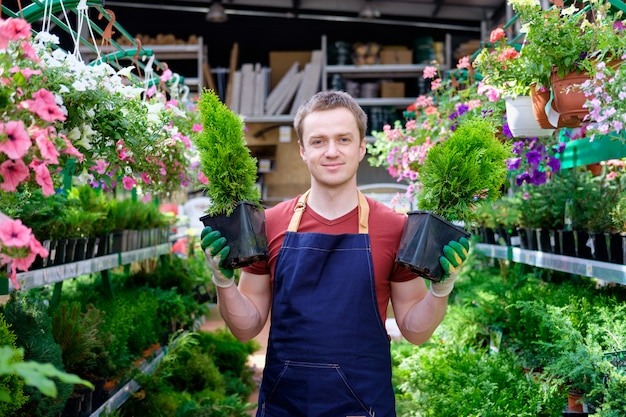 Vendedor de jovem em estufa de mercado de plantas no trabalho, florista Foto Premium
