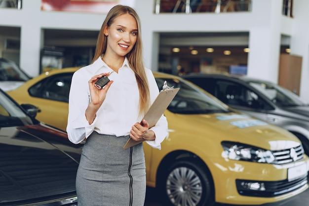 Vendedor de jovem feliz perto do carro com as chaves na mão Foto Premium
