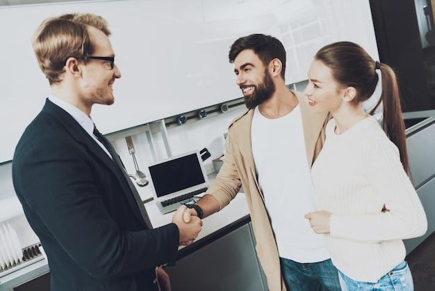 Vendedor e cliente com a esposa estão apertando as mãos na cozinha Foto Premium