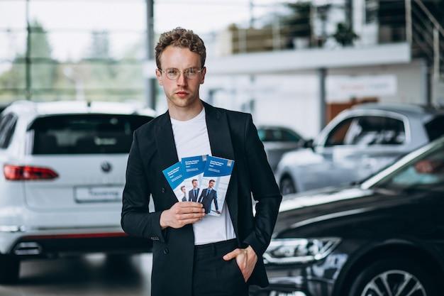 Vendedor em um showroom de carro com folhetos de negócios Foto gratuita