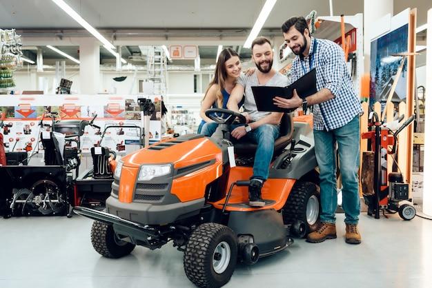 Vendedor está mostrando para casal nova máquina de limpeza na loja Foto Premium