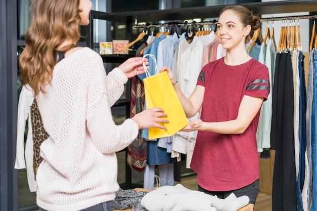 Vendedor feminino dando amarelo sacola para mulher Foto gratuita