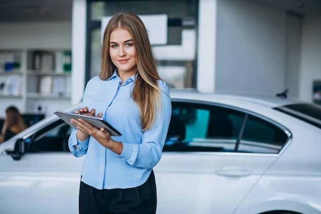 Vendedor feminino em um showroom de carro ao lado do carro Foto gratuita
