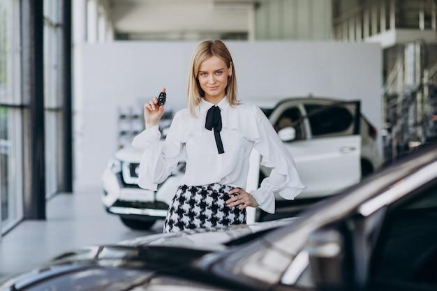 Vendedor feminino em uma sala de exposições de carro em pé ao lado do carro Foto gratuita