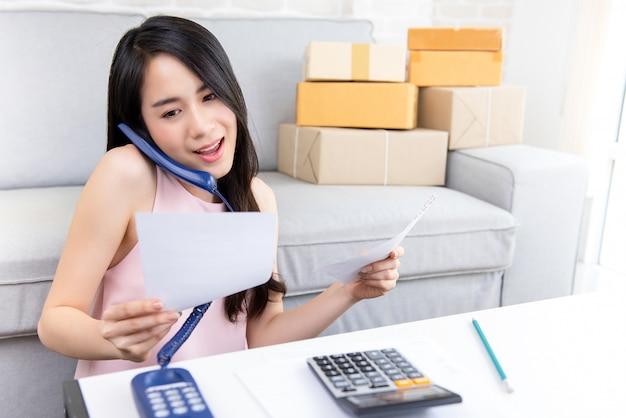 Vendedor freelance em linha da mulher que confirma ordens do cliente no telefone Foto Premium