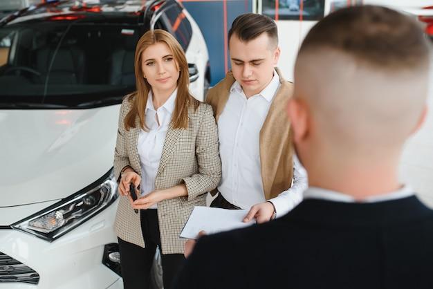 Vendedor maduro mostrando um carro novo para um casal no showroom Foto Premium