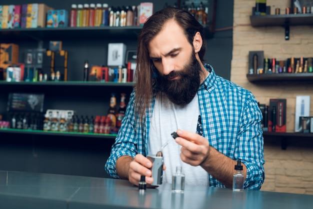 Vendedor na vipeshop mostra como encher o cigarro eletrônico. Foto Premium