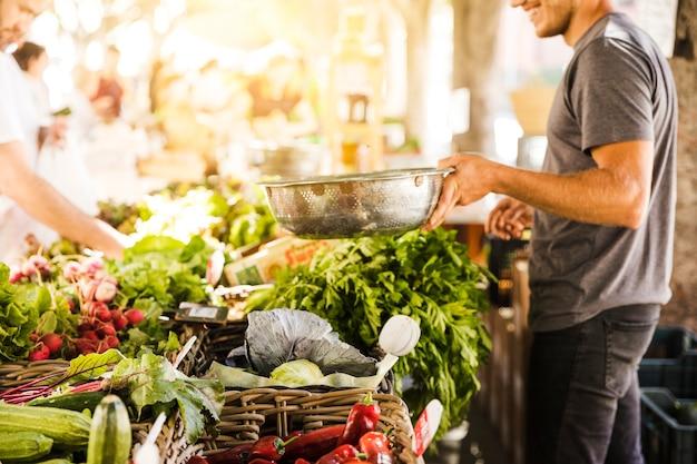 Vendedor vegetal de sorriso que vende o vegetal orgânico no mercado da mercearia Foto gratuita