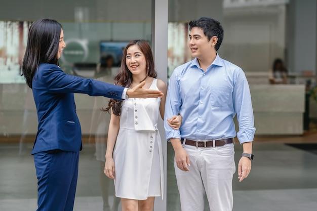 Vendedora asiática congratulando-se com o cliente de casal para verificar o carro na frente do showroom, Foto Premium