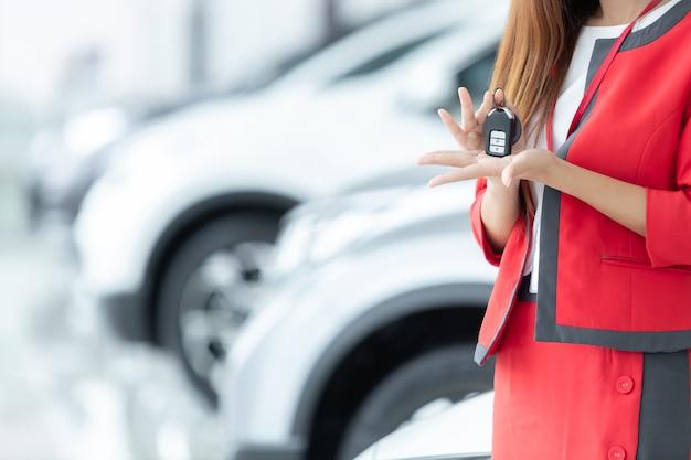 Vendedora asiática que dá a chave do carro sobre o fundo da feira automóvel, auto negócio, venda do carro. Foto Premium