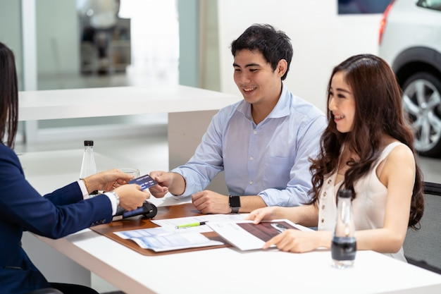 Vendedora asiática, recebendo, cartão crédito, de, par, cliente, quando, decisão, comprar, a, novo, car Foto Premium