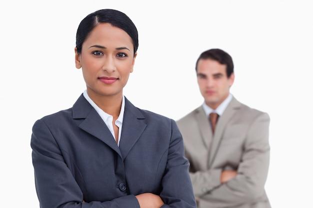 Vendedora com braços cruzados e colega atrás dela Foto Premium