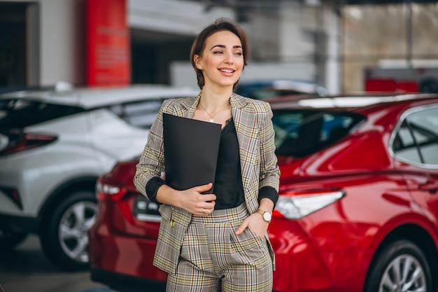 Vendedora de carro em um showroom de carro Foto gratuita
