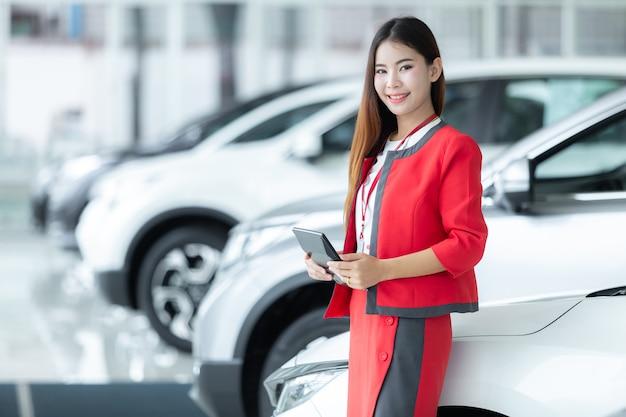 Vendedora nova asiática do carro que guarda a calculadora com uma exposição bem-vinda na sala de exposições. Foto Premium