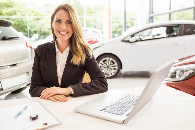 Vendedora sorridente atrás de sua mesa no showroom de carros novos Foto Premium