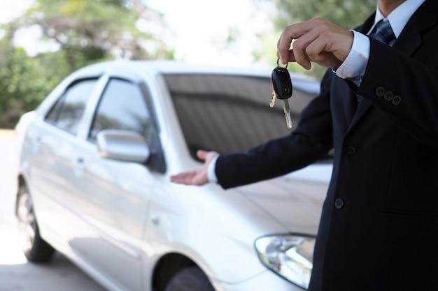 Vendedores de carros e chaves apresentando negociação de carro Foto Premium