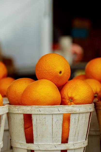 Vendendo laranjas frescas em cestas de mercado do fazendeiro Foto Premium