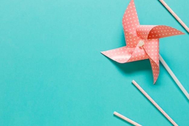 Ventilador de papel e palhas na superfície colorida Foto gratuita