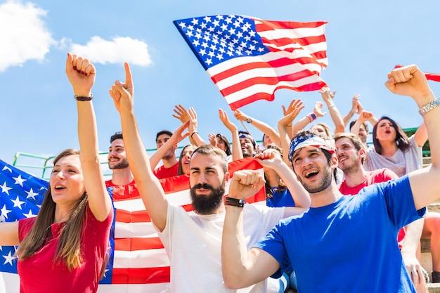 Ventiladores americanos torcendo no estádio com bandeiras dos eua Foto Premium