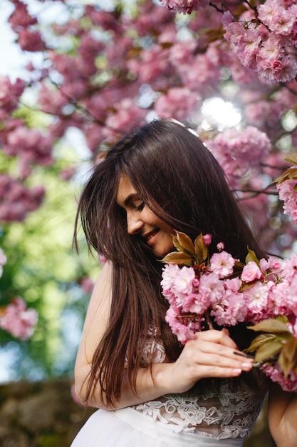 vento-sopra-cabelo-de-mulher-morena-enquanto-ela-coloca-antes-de-uma-arvore-de-sakura-florescendo_8353-7290.jpg