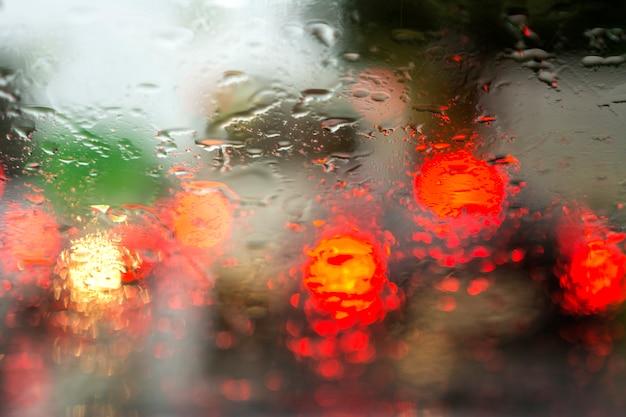 Ver através do vidro do carro sobre as luzes dos carros na chuva. borrão em vidro molhado. Foto Premium