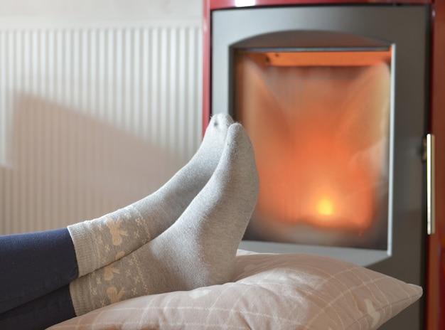 Ver os pés de uma mulher em meias relaxantes em frente ao calor de um fogão a lenha Foto Premium