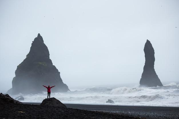 Verão, mulher em um pé de casaco rosa em uma praia de areia preta na islândia Foto Premium