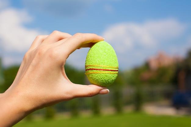 Verde brilhante lindo ovo de páscoa na mão no fundo do céu azul Foto Premium