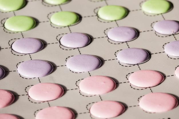 Verde; conchas de macaroons de rosa e roxas em um tapete de deslizamento Foto gratuita