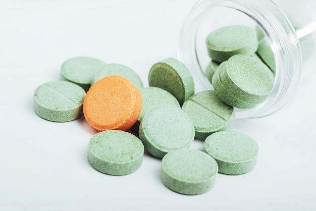 Verde médico e um comprimido laranja para o tratamento e cuidados de saúde em um fundo branco Foto Premium