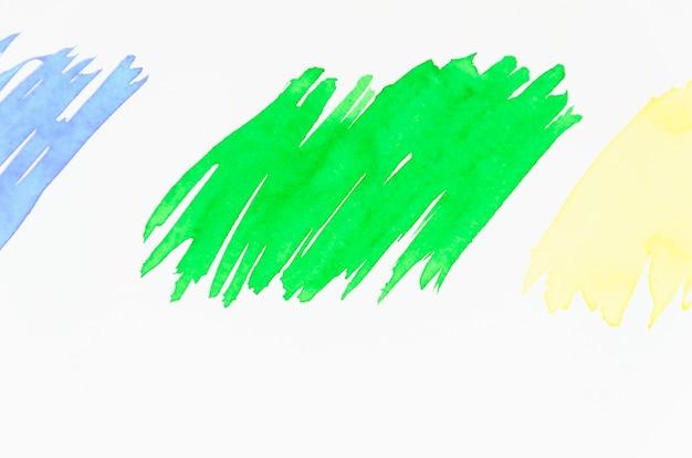 Verde; pincelada azul e amarela sobre fundo branco Foto gratuita