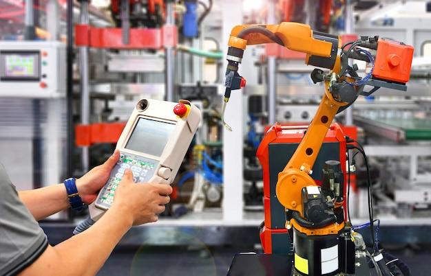 Verificação de engenheiro e controle automação laranja moderno sistema de robô na fábrica, indústria robô. Foto Premium