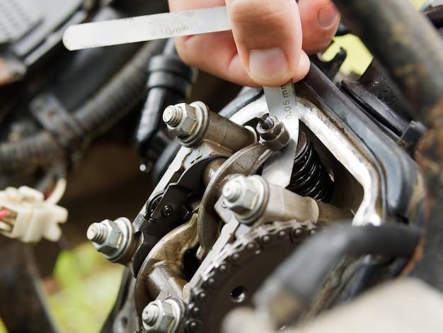Verifique a folga da válvula na scooter. Foto Premium