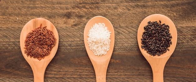 Vermelho; arroz marrom e branco na colher sobre fundo de madeira Foto gratuita