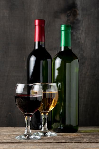 Vermelho e branco em copos ao lado de garrafas Foto gratuita