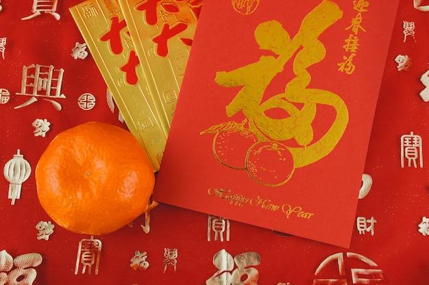 Vermelho e cartão de ouro ao lado de uma laranja Foto gratuita