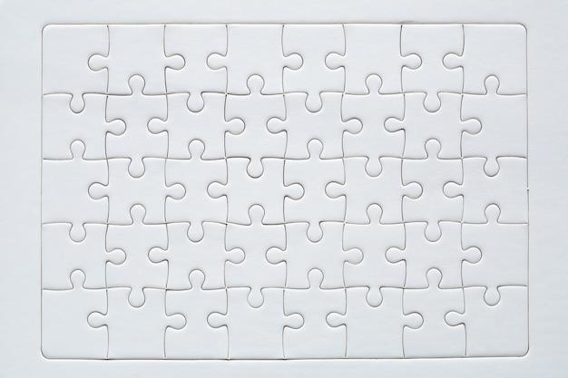 Vermelho inacabado com peças de quebra-cabeça branco Foto gratuita