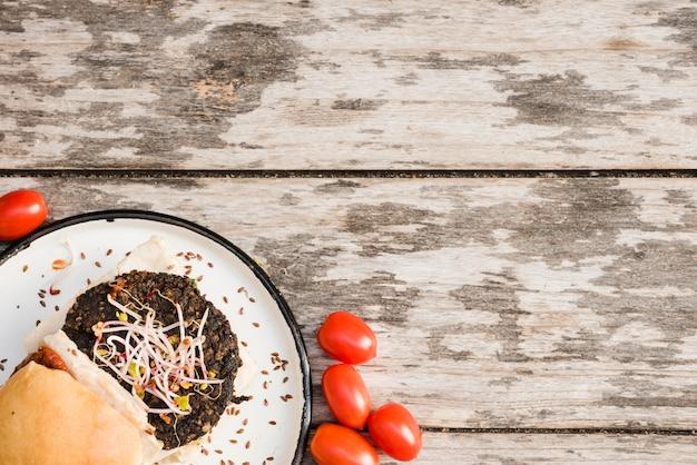 Vermelho, tomates, e, veggie, quinoa, hambúrguer, com, brotos, e, linho, sementes, ligado, prato branco, sobre, a, tabela Foto gratuita