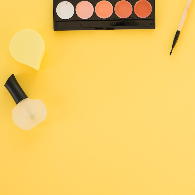 Verniz para unhas; paleta de esponja e sombra, disposta em uma linha em fundo amarelo Foto gratuita