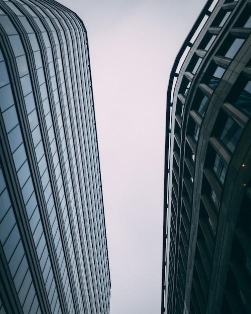 Vertical ascendente dos edifícios comerciais modernos altos, com um céu branco Foto gratuita