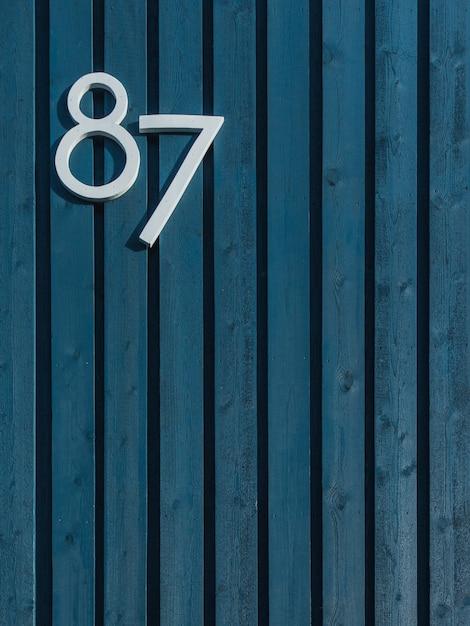 Vertical de uma parede azul de madeira com paus dispostos verticalmente e branco número oitenta e sete Foto gratuita