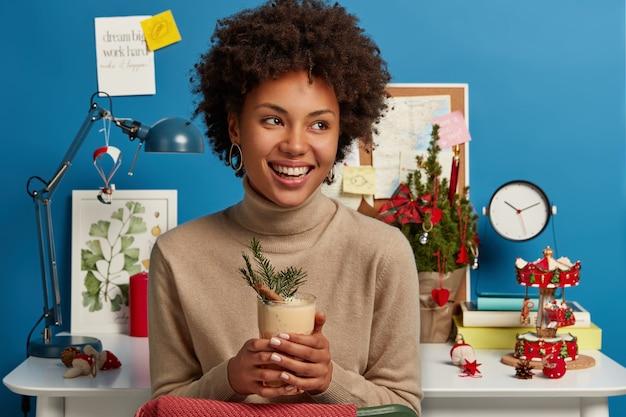 Véspera de natal, bebida tradicional e preparação de férias. mulher alegre com penteado afro segurando um copo de coquetel de gemada e sorrindo Foto gratuita
