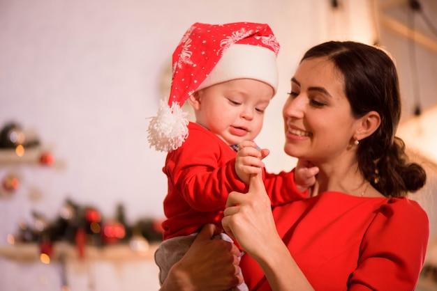 Véspera de natal. família mãe e bebê no jogo de hatplay de papai noel em casa perto da lareira Foto Premium